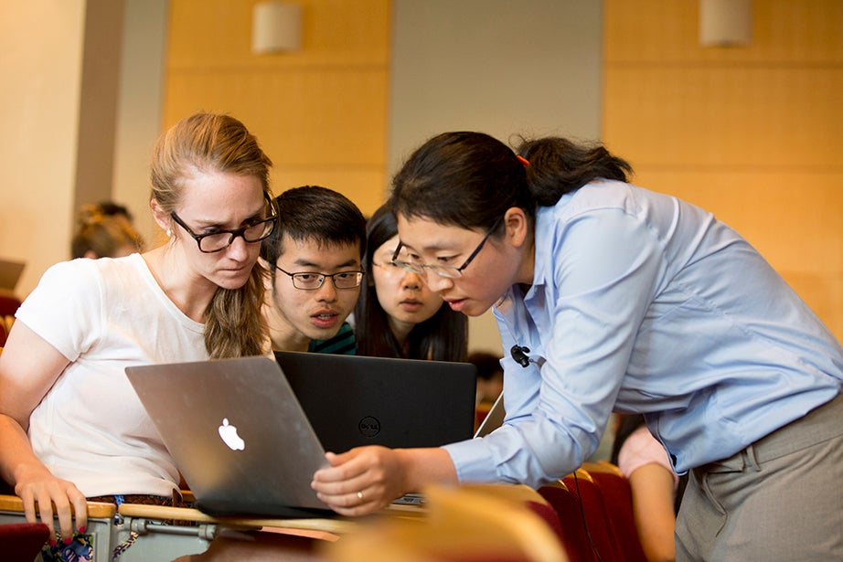 Mary-Grace Reeves '16 (from left) and first-year Graduate School of Arts and Sciences students Wedding Xu and Xiao Yang get help from Kang-Kuen Ni during his chemistry course. Rose Lincoln/Harvard Staff Photographer