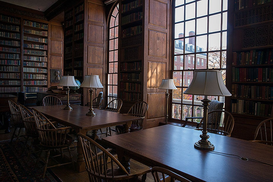 Matching lamps line wooden tables in Dunster's library.