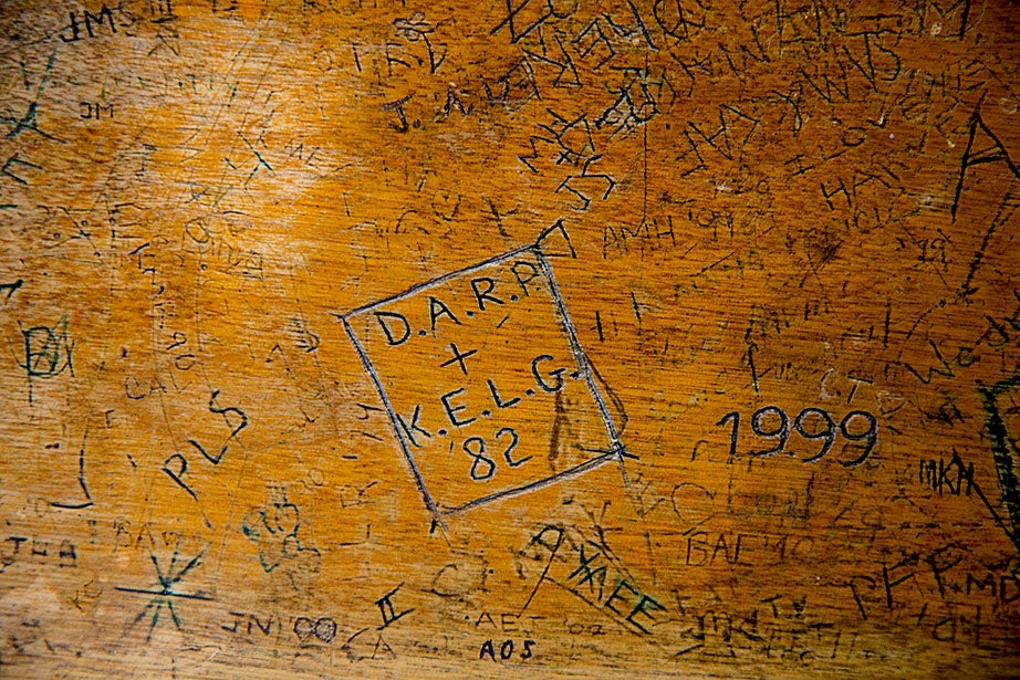 Years of student engravings cover a third floor oak table in the Hicks House library.