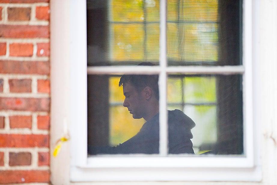 A leaded glass window frames Taylor Carol '17.