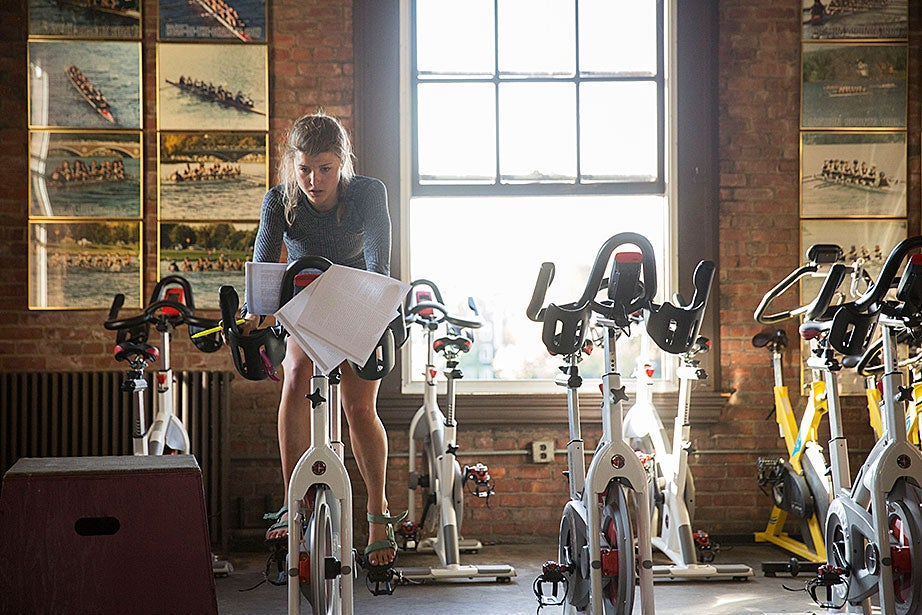 Radcliffe lightweight crew team member Marina Felix '19 does coursework while spinning on a bike machine.