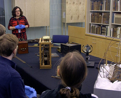 Professor Sara Schechner shows students compasses, sextants, and a variety of other instruments that sailors used to measure and predict their location at sea.