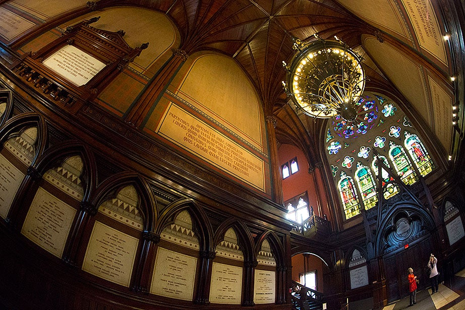 """Memorial Hall's transept and stained-glass windows by Sarah Wyman Whitman were donated in memory of the """"sons of Harvard"""" who gave their lives in the Civil War and whose names are recorded in the transept's tablets."""