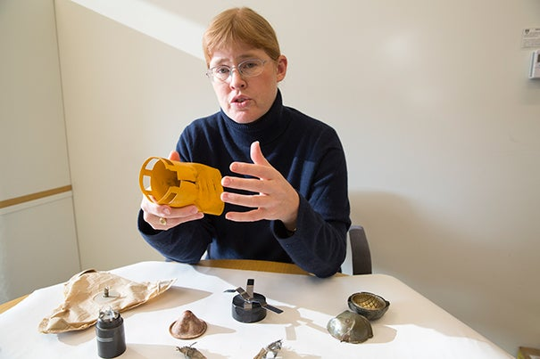 """Bonnie Docherty, a senior instructor at Harvard's International Human Rights Clinic, traveled to Geneva to advocate for stronger regulations on incendiary devices, which she calls """"exceptionally cruel weapons."""" Here she shows inert pieces of cluster munitions, another inhumane weapon, which she helped ban."""