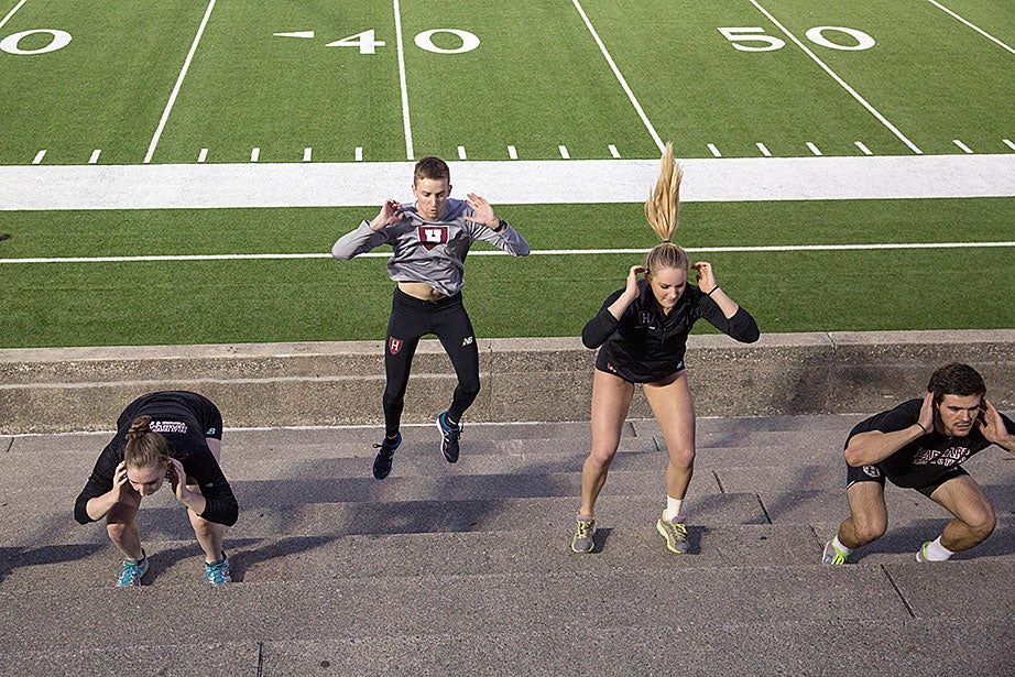 Injured members of the Harvard track and field team, restricted from running the steps, do standing two-legged hops up the seats under the stadium lights. Lucy Alexander '18 (from left), Spencer Lemons '16, Raegan Nizdil '17, and Brett Henderson '17 exhibit various stages of hopping.
