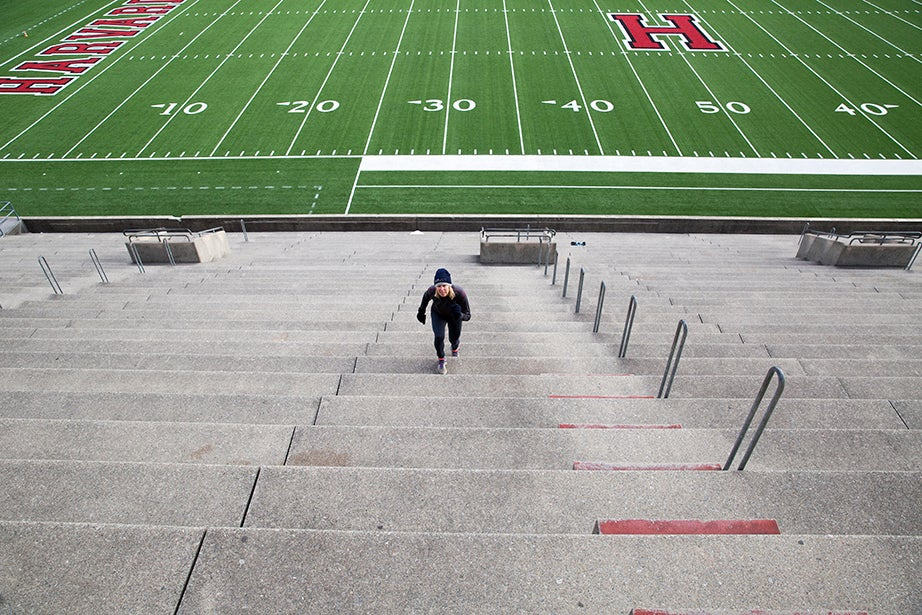 """Jenny Frutchy, Ed.M. '82, a spry 61 years young, appears dwarfed by a sea of steps as she makes her way up a row of seats. """"I hike the seats for half an hour, then I go swim a mile at Blodgett. I do the steps as conditioning for skiing, which I do all winter,"""" she says."""