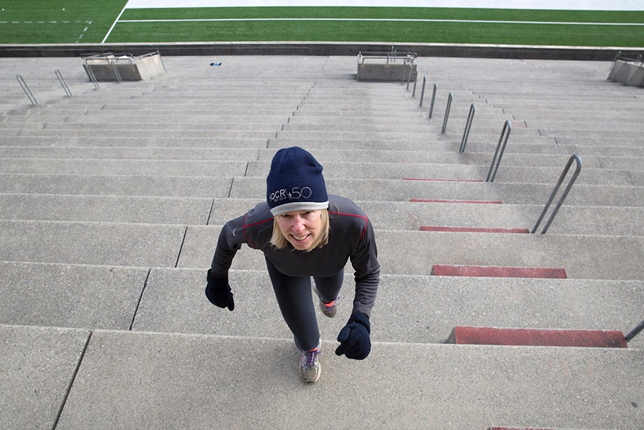"Jenny Frutchy, Ed.M. '82, flashes a satisfied smile after reaching the top. ""Around here I ride my bike everywhere I go, but if it's lousy weather, and I don't want to ride, the stadium is always there, staring you in the face. I like to mix up my exercise; I've been doing the steps for about ten years,"" she says."