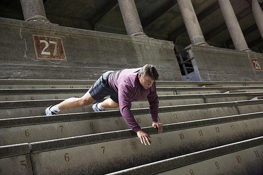 "Steve Zolud does a bear crawl down the steps, part of his training for recreational boxing. ""Toward the end of my run I usually do a crawl down the last three or four rows. Tyler's not as big a fan of the bear crawl as I am,"" Zolud says of his son."
