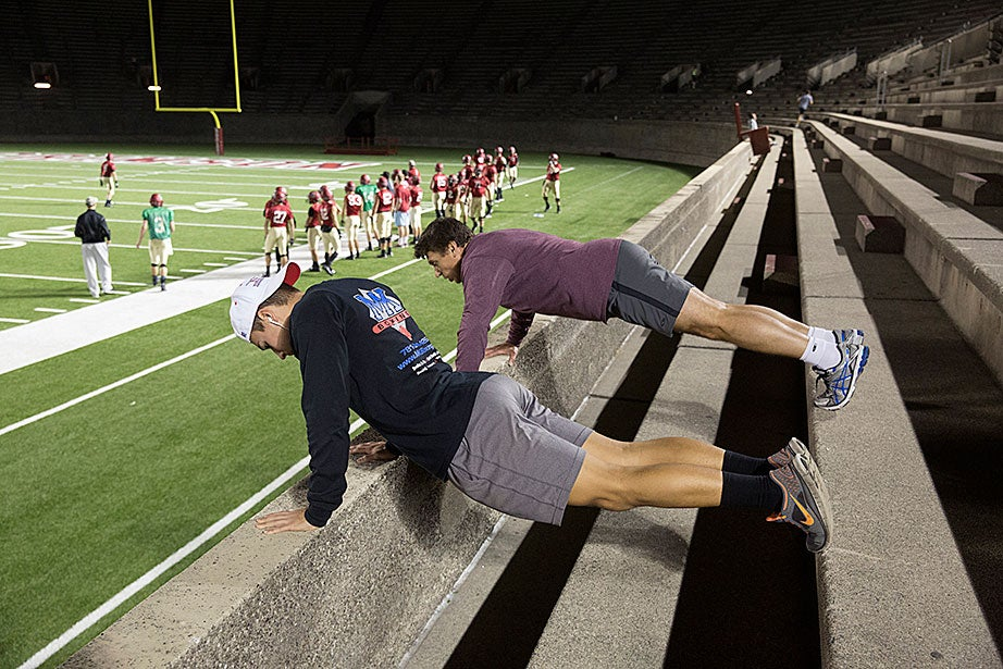 """Steve Zolud, top, who works at M.I.T., previously worked at Harvard for five years as a business analyst at HUIT. He and his son Tyler both box in Woburn, but come to the stadium to run the steps weekly. Father and son do a set of push-ups between running rows of steps to mix in different kinds of conditioning. """"We run the steps, we hop them, we might walk a few, and we do push-ups in between,"""" Steve Zolud says. The football team is practicing on the field behind."""