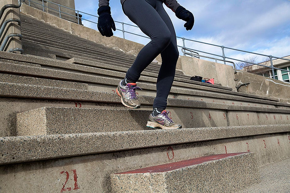 A step climber descends a row of steps between sets of walking up the steeper seats. Walking down the smaller steps is safer than running, and it provides a form of interval training that most climbers find helpful in building endurance.