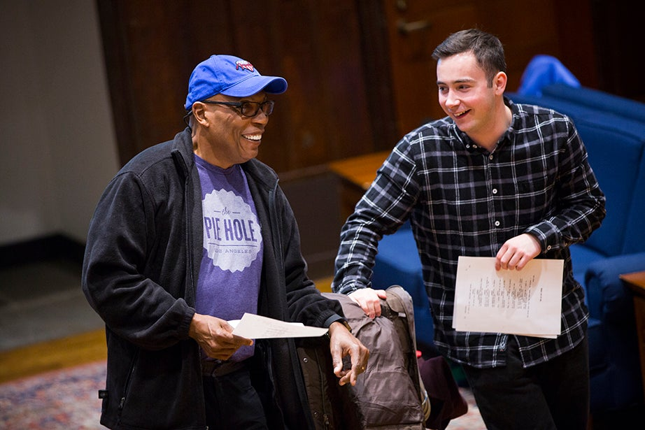"""Paris Barclay '79 (left) shows Connor Doyle '19 how to direct a scene. Later, Barclay shared a memory of his time as a student in the same Leverett House room, when Stephen Sondheim encouraged students to """"write about things that move you."""" Stephanie Mitchell/Harvard Staff Photographer"""
