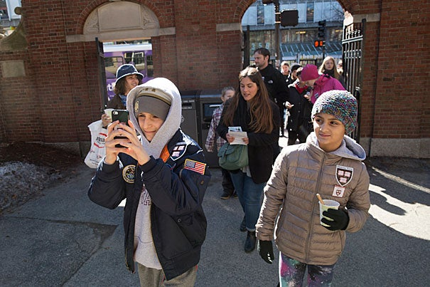 Anthony Mancuso (left), 12, follows Harvard's official interactive online tour app  as his sister, Sophia, 8, looks on. The Mancusos traveled from Westchester County, New York, to scope out Harvard.