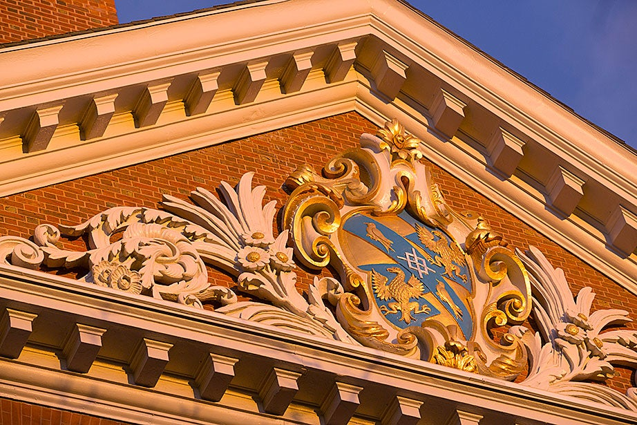 A Dunster House roof shield with bird motifs glows gold in the sunset. Kris Snibbe/Harvard Staff Photographer