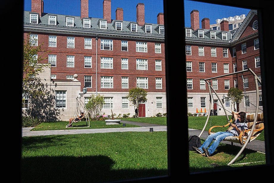 Students use social media on swinging chairs in the Dunster House courtyard. Kris Snibbe/Harvard Staff Photographer