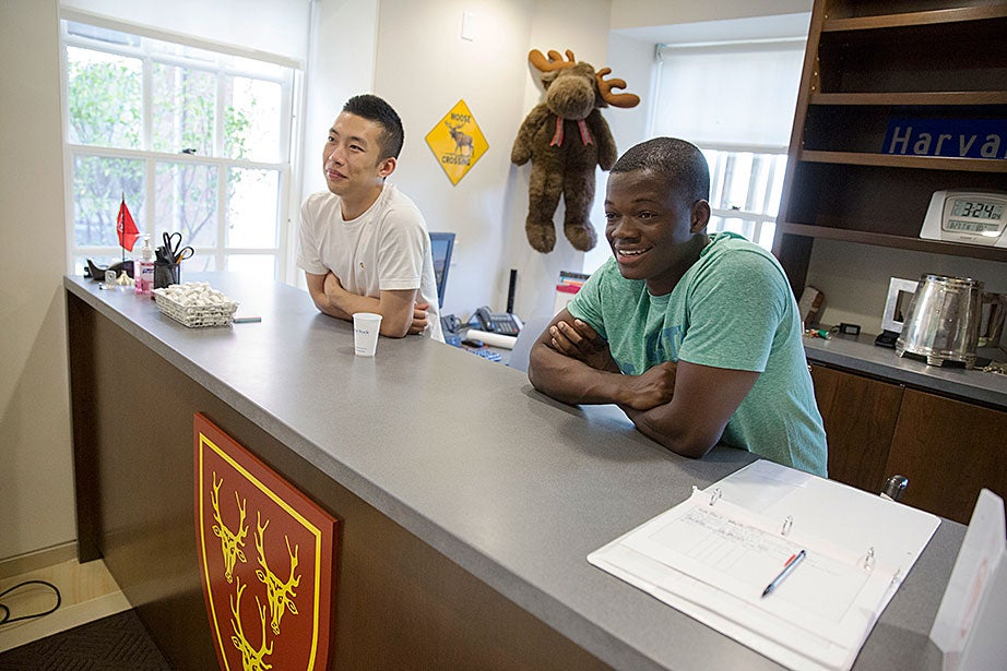Roommates Kevin Chen '17 (left) and Ayomide Opeyemi '17 greet tour groups in the building manager's office inside Dunster House. Kris Snibbe/Harvard Staff Photographer