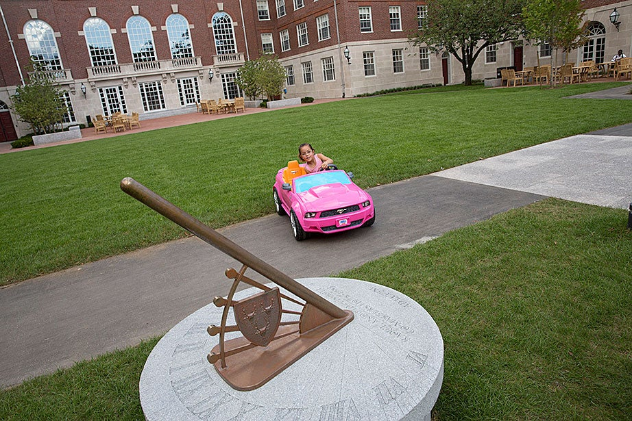 Isabella Diaz, daughter of resident dean Carlos Diaz and his wife, Martha Diaz, a teaching assistant in romance languages and literatures, drives her toy electric car past a sundial in Dunster House courtyard. Kris Snibbe/Harvard Staff Photographer