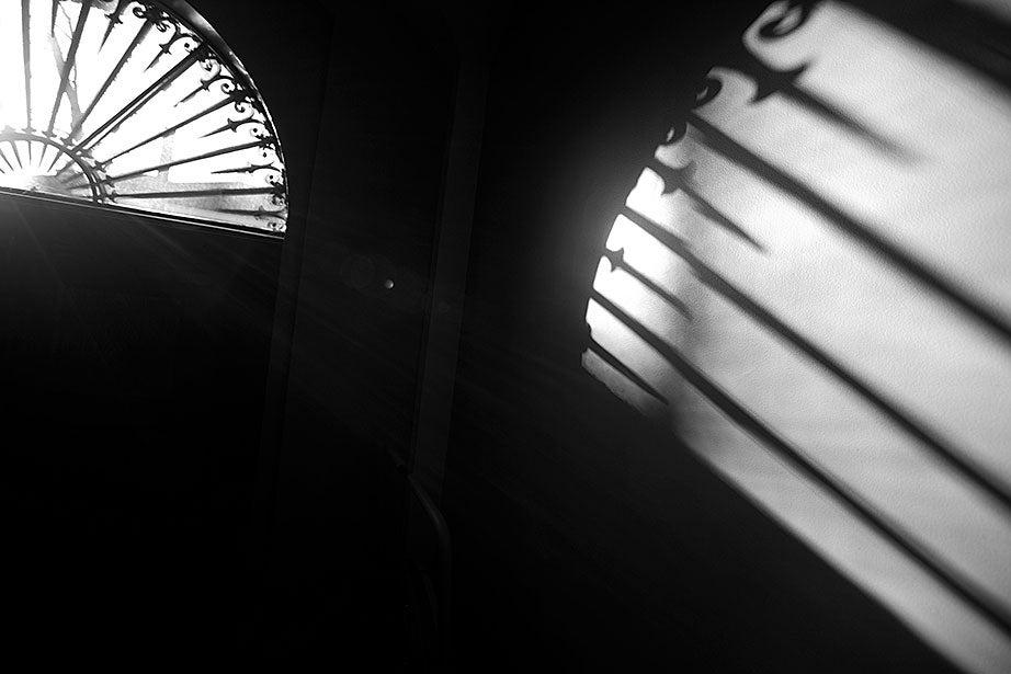 Inside Busch Hall, a fan window casts an elongated shadow on a nearby wall.
