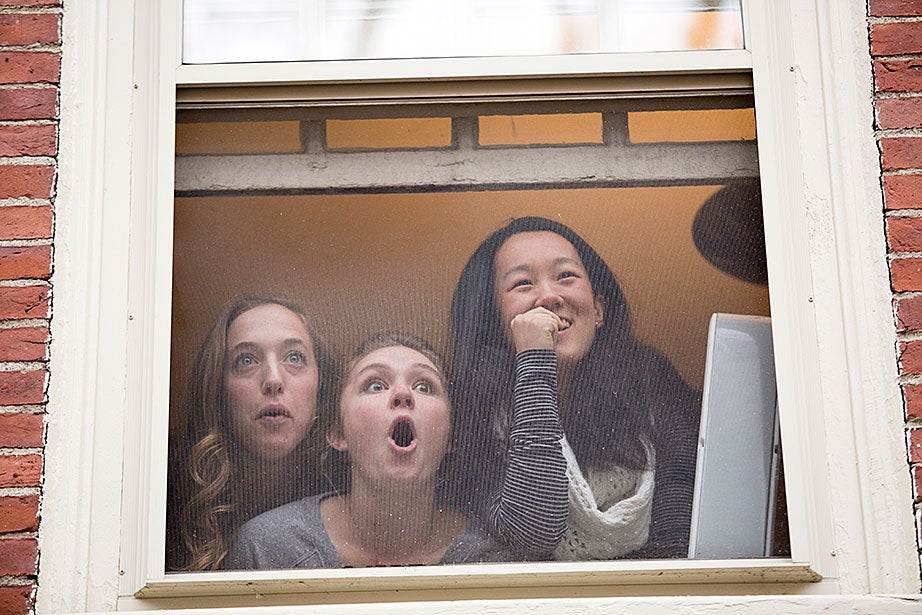 Hannah Natanson (from left), Grace Wagner, and Liz Roux watch from their window in Straus as upperclassmen deliver housing assignments. They kiddingly said they were hoping for anything but PfoHo. Rose Lincoln/Harvard Staff Photographer