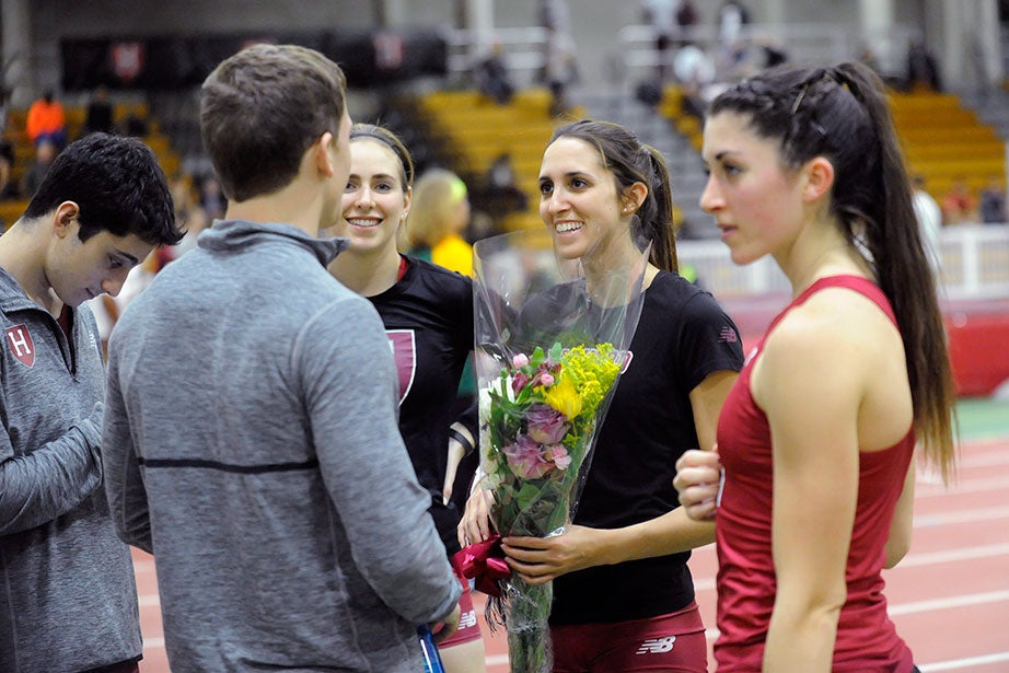 Pole vaulter Lexi Schachne '16, second from right, talks with track and field teammates after receiving flowers as part of a Seniors' Day celebration.