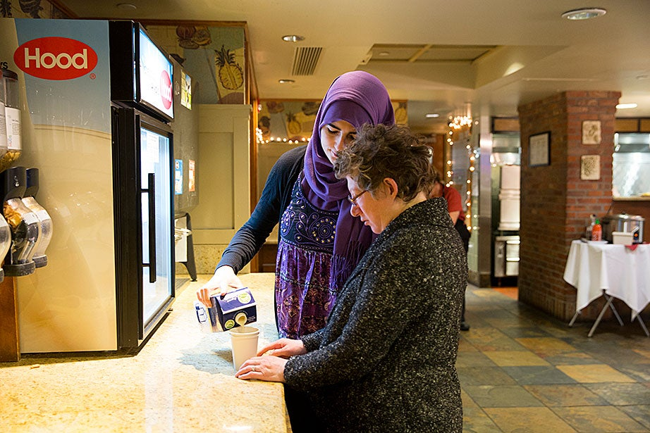 Fatima Bishtawi helps Amy Richmond find soy milk for her coffee.