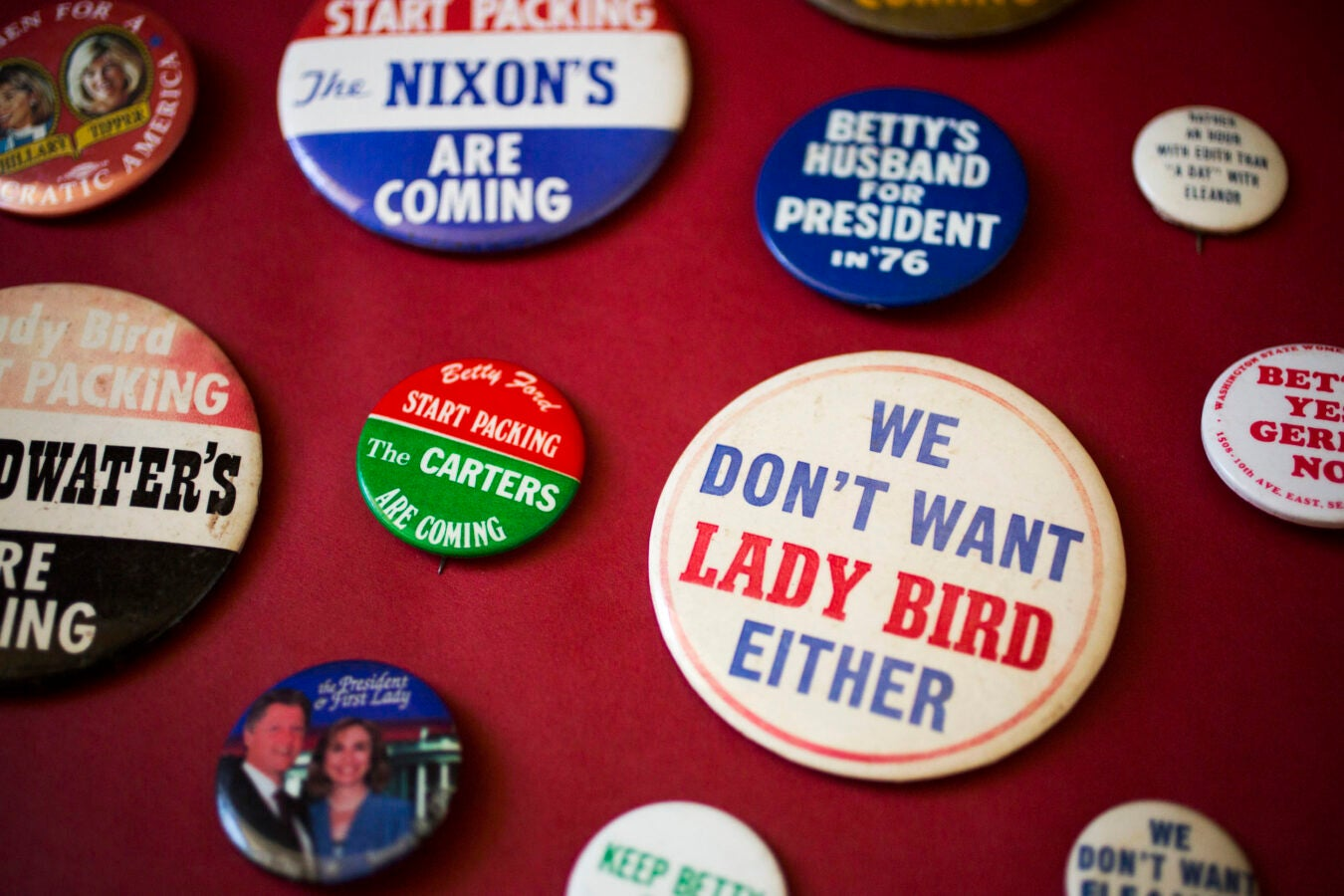 Campaign buttons feature candidate spouses.