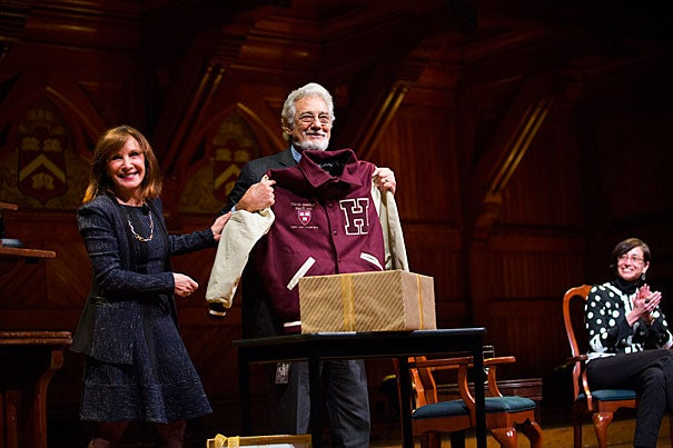 """Opera singer Plácido Domingo spoke about his career in a conversation at Sanders Theatre called """"Giving Voice."""" Diana Sorensen (left), dean of arts and humanities, presented Domingo with a Harvard jacket. Professor Tamar Herzog (right) also participated in the conversation."""