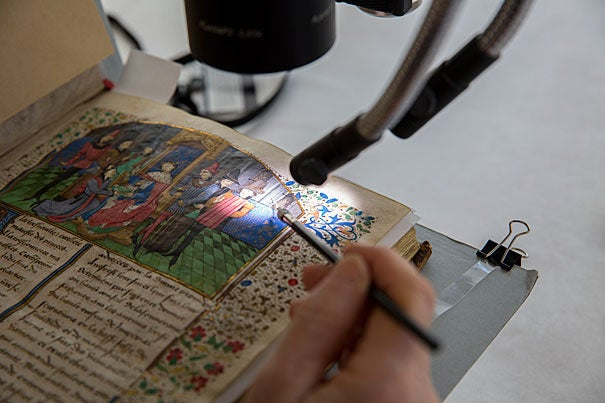 Book conservator Catherine Badot-Costello uses a microscope to work on an illuminated, bound parchment manuscript from Houghton Library.
