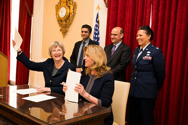 Harvard President Drew Faust (left) and Secretary of the Air Force Deborah Lee James celebrate the return of the Air Force ROTC program to campus with a ceremonial signing.