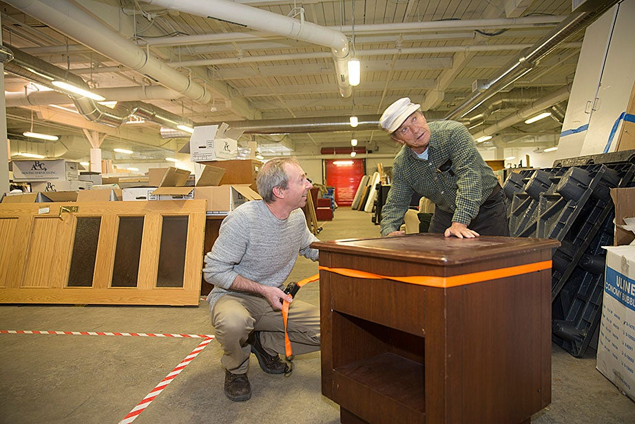 """Kieran Clyne, operations supervisor for landscape and recycling, and Franco Camporesi, volunteer and Allston resident, repair a donated table at the Harvard Recycling and Surplus Center at 156 Western Ave., Allston. The University prioritizes the reuse of furniture and other materials through donations to more than 200 local organizations, """"freecycle"""" events, and by distributing surplus furniture and equipment to the community at the Recycling and Surplus Center."""