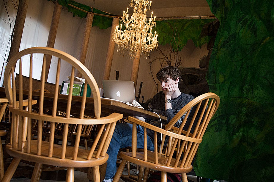 """Philipp Nowak '18 studies in the Lowell House dining hall after breakfast. He loves the yellow walls of the dining room. """"I like the color,"""" he said. """"It's friendly!"""""""