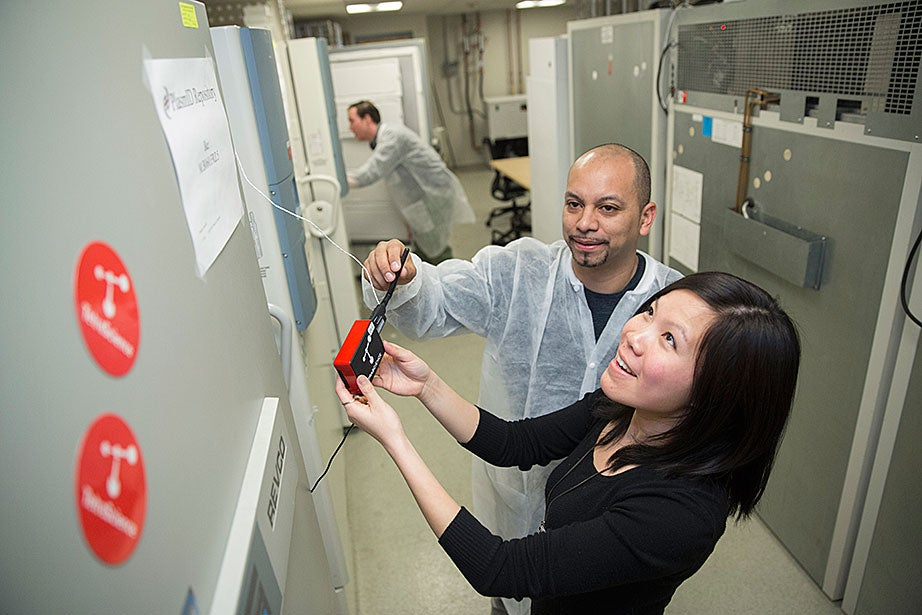 William Veguilla (left), a research assistant, and Li Qiong Chan (right), operation director of the DNA Resource Core at Harvard Medical School, work with TetraScience equipment connected to ultra-low-temperature freezers at HMS. The devices, developed by a team that included Harvard students and supported by a student sustainability grant, were developed to help researchers monitor and reduce energy using wireless technology. In the background is research assistant Alexander Reynolds.