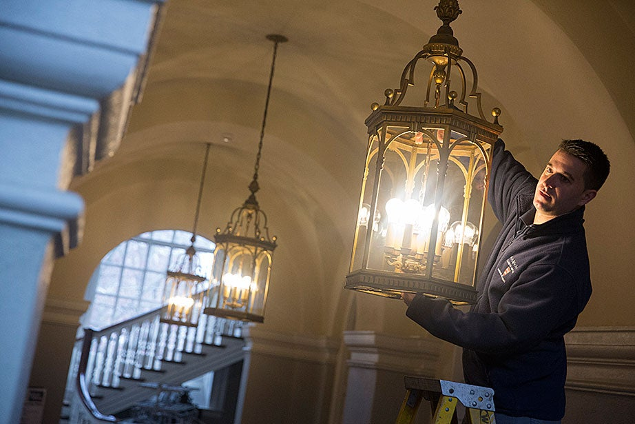 Memorial Church's property operations assistant, Jim Barbas, maintains historic chandeliers that were recently outfitted with long-lasting, energy-efficient LED light bulbs in the narthex entrance in Harvard Yard.