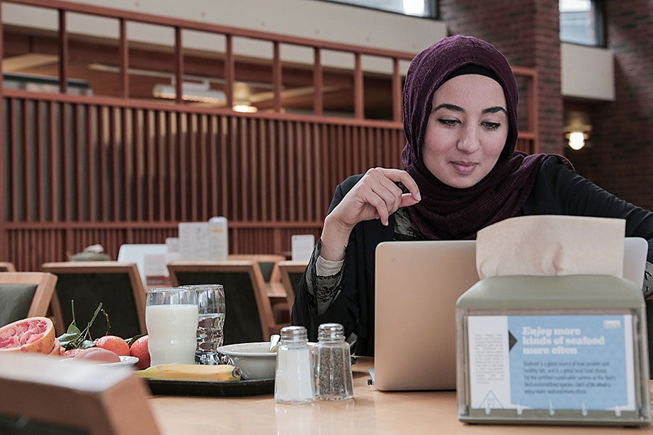"""Hanaa Masalmeh '18 often reads inside the Mather House dining hall in the morning. """"The dining hall is super-active on Friday morning because a lot of people don't have classes on Friday mornings and they all come to the dining room to study,"""" she said."""