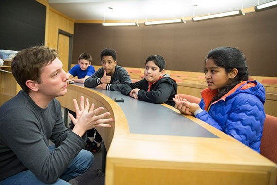"Michael Gerhardt, (from left) Research Assistant in the School of Engineering and Applied Sciences gives an ""organic mega flow battery"" demonstration to Harlan Altipeter, Steven Noel, Anish Kanade, and Oviya Selvam, all seventh grade students from the Cambridge Street Upper School during a campus with Project Teach inside the Maxwell Dworkin building. Project teach works with teachers, students and families, to provide on-campus academic experiences for all 7th-grade students from Cambridge Public Schools (CPS) at Harvard University. Kris Snibbe/Harvard Staff Photographer"