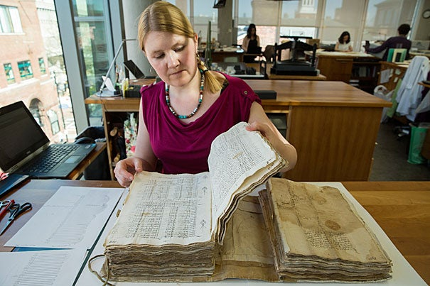 Book conservator Katherine Beaty works on a bound volume of business records, including partnership agreements and other related documents from the Medici Collection, at the Weissman Preservation Center. Jon Chase/Harvard Staff Photographer