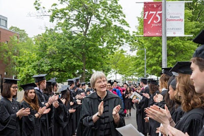President Drew Faust applauds the seniors processing to the Phi Beta Kappa Literary Exercises.
