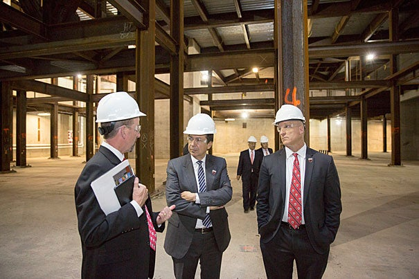 Francis Doyle (from left), dean of SEAS, tours the School's building site in Allston with John A. Paulson MBA '80 and FAS Dean Mike Smith. Kris Snibbe/Harvard Staff Photographer