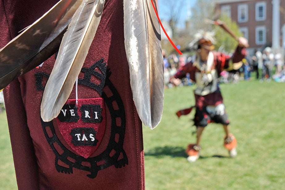 A banner bearing the Veritas turtle symbol of the Harvard University Native American Program (HUNAP) frames a dancer in Radcliffe Yard. The annual Harvard Pow Wow, now in its 21st year, honors Native American culture with traditional songs and dance. Participants include Native Americans from Harvard and members of tribes from across the United States and Canada.