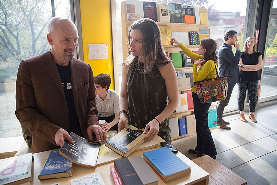 """Jeffrey Schnapp (left), founder/faculty director of metaLAB and faculty co-director of the Berkman Center for Internet & Society, and Sarah Newman, artist in residence at metaLAB, look through books at the exhibition and release of """"Blueprint for Counter Education."""""""