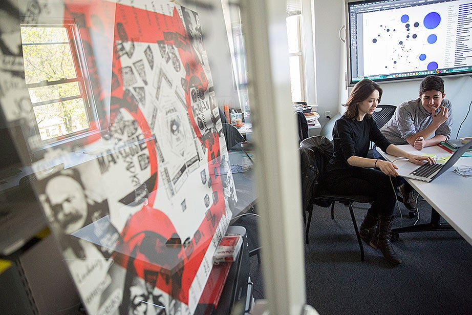 "Krystelle Denis (left), HGSD '15, a researcher and designer, and Jessica Yurkofsky, principal and creative technologist, work on data visualizations inside the metaLAB office and studios. They are in the early stages of a metaLAB project called ""Curricle,"" which will offer novel ways to search and discover patterns in course registration, student interests, and the history of the liberal arts."