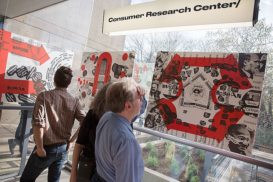 """Audience members look through books at the exhibition and release of an expanded edition of """"Blueprint for Counter Education"""" at the Consumer Research Center/bookshop at the Carpenter Center."""