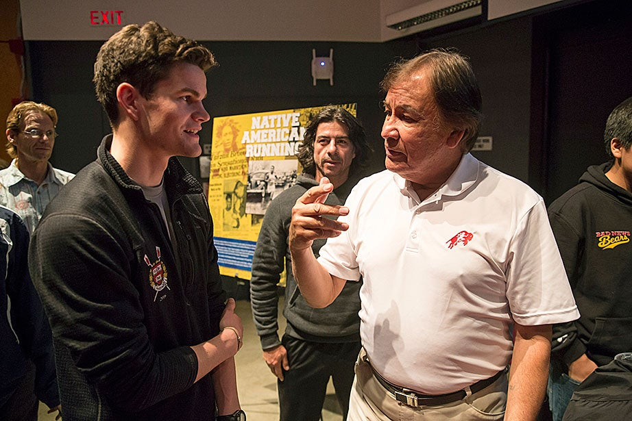 Miles Graham '16, left, speaks with 1964 Olympic gold medalist Billy Mills (Oglala Lakota). For Mills, running was not an end in itself, but a vehicle for building bridges between people of different cultures and religions. At age 77, Mills is on the road more than 300 days a year with his foundation Running Strong for American Indian Youth, promoting the physical and spiritual benefits of running for indigenous people in the United States and around the world.