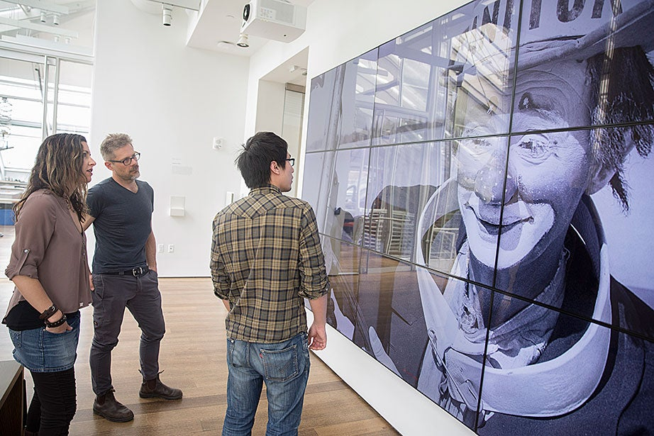 "Sarah Newman (from left) and Matthew Battles work with technology fellow Ming Tu on ""Your Story Has Touched My Heart."" The photo of the clown is a sample image used to test the screen. ""The team's projects infuse traditional modes of academic inquiry with an enterprising spirit of hacking, making, and creative research,"" says Battles."