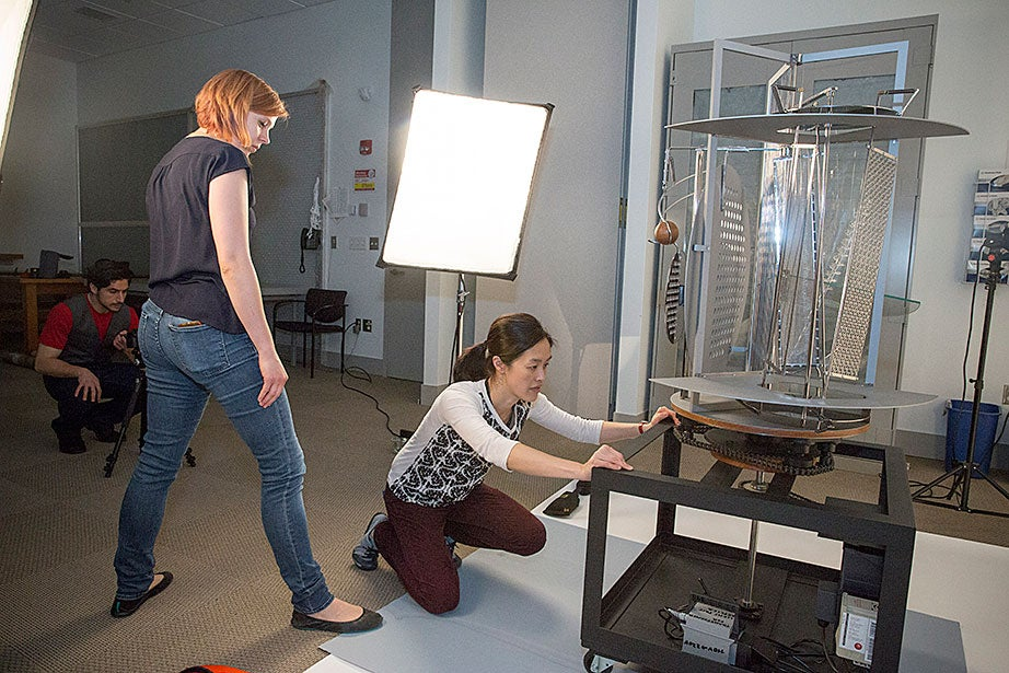 """Cristoforo Magliozzi (far left), metaLAB principal, and Alexandra van den Berg (center), museum installer/art handler, work with Angela Chang to make an interactive video of a replica of László Moholy-Nagy's """"Light Prop for an Electric Stage."""""""