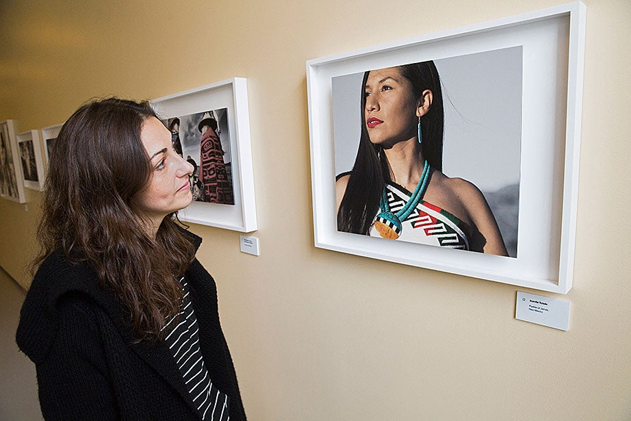 "Exhibit assistant Giorgia Cannici looks at Matika Wilbur's portrait of Juanita Toledo of Jemez Pueblo, N.M., at the Johnson-Kulukundis Family Gallery in Byerly Hall at Radcliffe. ""I really love Matika's work,"" Cannici says. ""She is an incredible communicator, both through her photography and her words. So many people passed by the exhibition after having heard her talk and told me how moving her words were and how much they were impressed by her contagious joy."""
