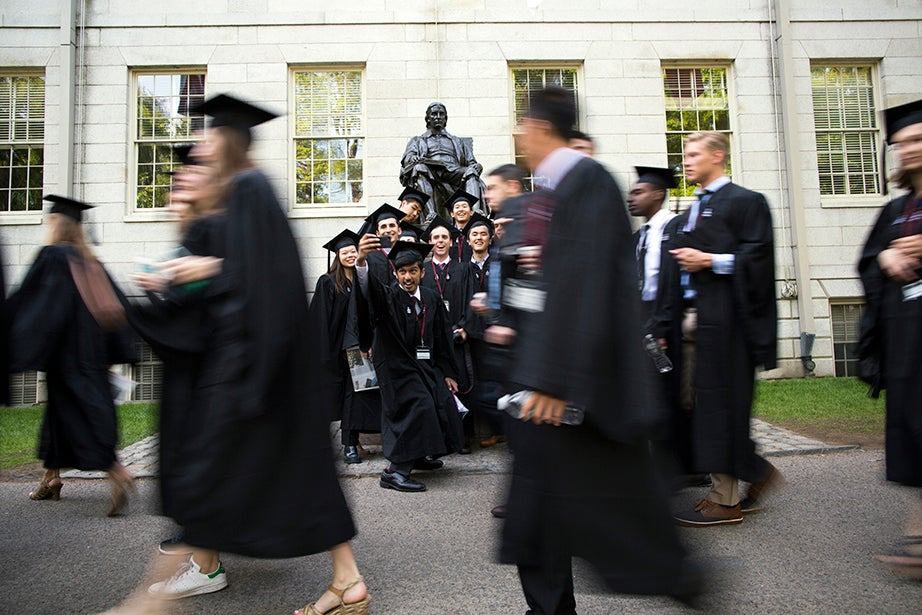 Graduates pause for a photo while passing the John Harvard Statue. Stephanie Mitchell/Harvard Staff Photographer