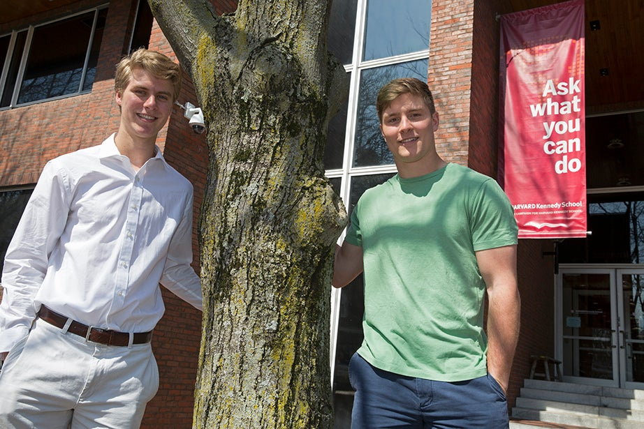 """Harvard sophomores Nicholas (left) and Beau Bayh '18 are twins from Indiana. Both have an interest in politics and social service, as well as athletics. They stand at the entrance to the Harvard Kennedy School in front of a sign that reflects their desire to serve: """"Ask what you can do."""" Jon Chase/Harvard Staff Photographer"""