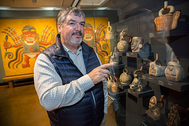 Luis Castillo, standing before ceramic pots depicting women on display at the Peabody Museum, discusses his research on high-status burials featuring female priestesses in ancient Peru and female power in the Andean culture.