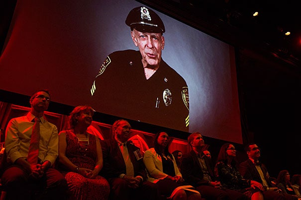 The image of Sergeant Dan Twomey appears above his fellow Harvard Heroes. Sixty-three University staff members were honored for their contributions to Harvard during a ceremony at Sanders Theatre.