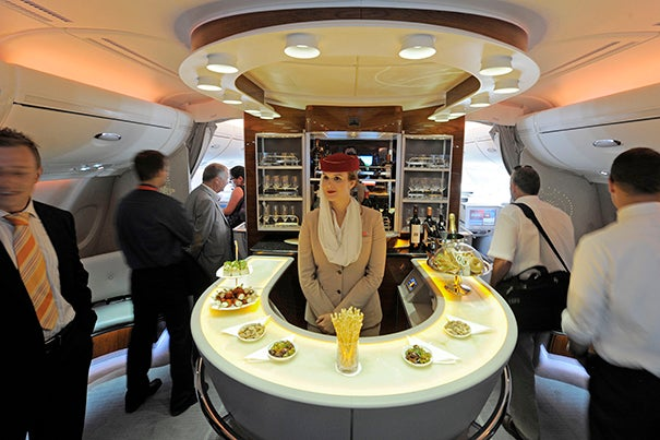 Stewardess Nadine Schumacher (center) works at the bar in the first-class section of an Emirates Airline Airbus A380 passenger plane. Research co-authored by Harvard Business School's Michael I. Norton has found that flights separating passengers into first- and economy-class cabins are more likely to see incidents of air rage.